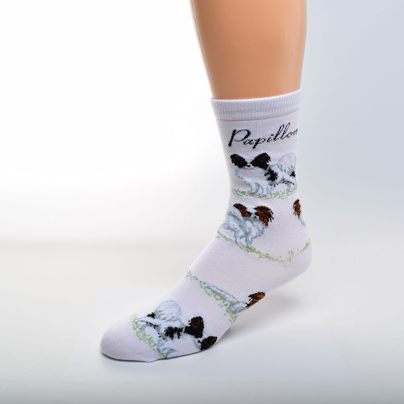 On a White background For Bare Feet Papillon Poses Sock begins. Under the Cuff reads, Papillon in Black Print. Black and White Papillons in a Stance pose are first. Then two reverse White and Red Papillons. A White and Red Papillons Laying Down is the Last Poses and the Pattern repeats.