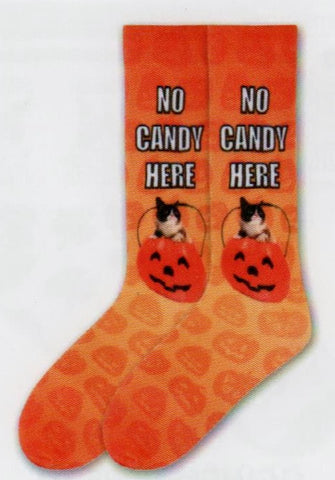 "Grumpy Cat Mens No Candy Here Sock starts on an Orange background. All over the Sock are Jack-O-Lanterns in Deep Carrot Orange. Then the Jack-O-Lantern Candy Cauldron that Grumpy Cat is popping out of is Orange Red. Its Handle, Eyes, Nose and Mouth are Black. Below the Cuff in White and Black Print reads, ""No Candy Here""."