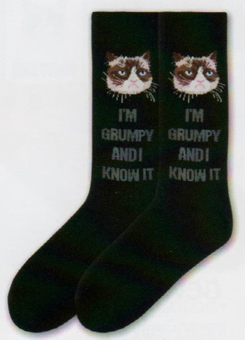 "Grumpy Cat Mens I'm Grumpy and I Know It Sock is on an all Black background. Under the Cuff is Grumpy Cat's Face in Cream and Chocolate with Blue Eyes and Pink Nose and Mouth. Under him is the saying that reads, ""I'm Grumpy And I Know It"" in Dark Grey Bold Print."