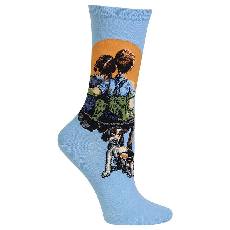 Hot Sox Womens Norman Rockwell Little Spooners Sock has a smaller Cuff than the Mens Sock. It is Sky Blue background. The Boy and Girl are spooning together watching the Moon. They are sitting on a makeshift bench with a puppy waiting for them.