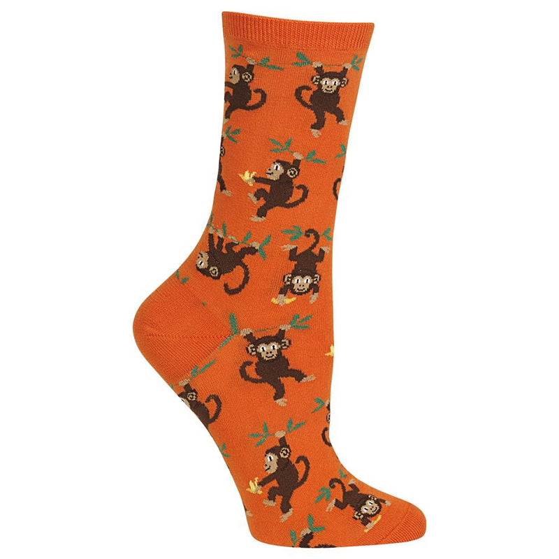 Hot Sox Womens Monkey Sock starts on a Bright Orange background. These Monkeys are hanging around with Hands and Feet, One Handed and just by the Tail. The body of the Monkey is Seal Brown and the Face, Hands and Feet are Brown. Their Eyes, Nose and Mouth plus Detail is in Black. Leaves and Limbs are Green. The Bananas are all Yellow.