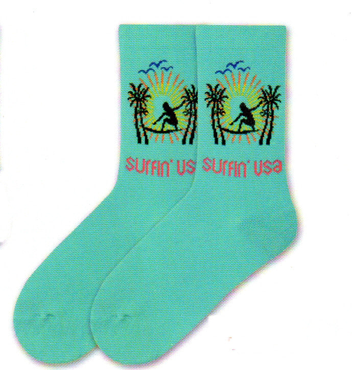 K Bell American Made Womens Surfin' USA is on a background called Jewel. A Silhouette of a Girl in Black is on a Surf Board. With Bright Yellow and Orange streams of light. Blue Silhouette of birds. To finish off the scene are Black Palm Tree Silhouettes.