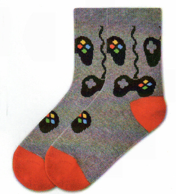 K Bell Boys Controls Sock starts on a Charcoal Heather background. The Heels and Toes are Bright Red. Game Controllers are the Controls on this sock. They are wired and wireless. On the Right Side are the 4 Buttons, Yellow, Blue, Red and Green. On the Left Side is the Grey D-Pad.
