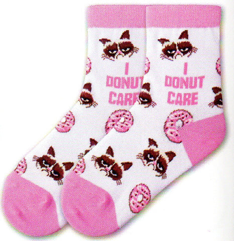 "K Bell Kids Grumpy Cat I Donut Care Sock comes in a White background with Pink Cuffs, Heels and Toes. Grumpy Cat has his picture interchanged in rows with Pink Iced Donuts. In the middle of the Sock is the Meme that says, ""I Donut Care""."