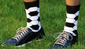 Play Soccer while in Soccer Ball Socks by K Bell. Black background with White and Black making the pattern of a Soccer Ball on a Model