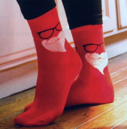 Model Wearing Secret Santa Socks Showing Fuzzy Beard in White Black Glasses and all Red Sock.