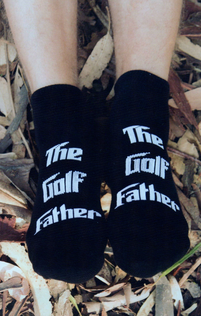 "Model wearing K Bell Mens The Golf Father sock. The Golf Sock is all Black then the Words are all White saying, ""The Golf Father""."