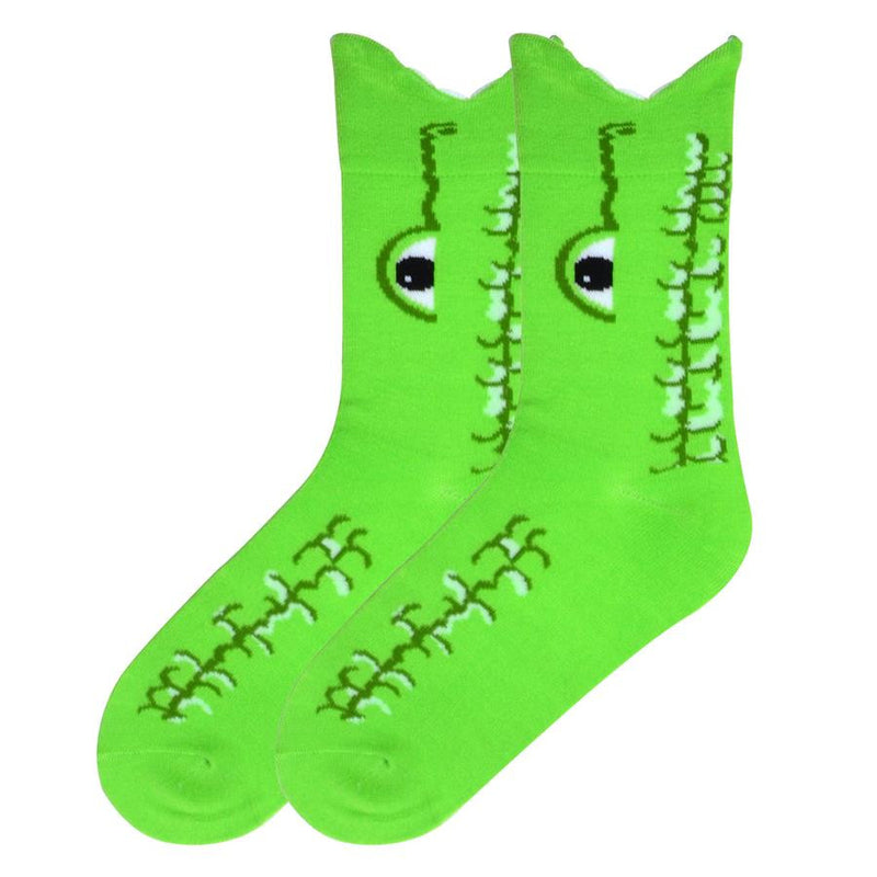 K Bell Womens Wide Mouth Alligator Sock is a Bright Green as the background color. White puffy yarn are the teeth. The eye is Black and White with Dark Green outlining also showing its snout. Dark Green and Cream also show the scaley texture of the Alligator's hide.