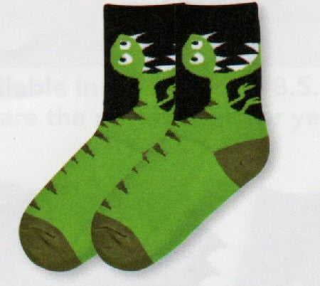 K Bell T-Rex Kids Socks are upper Black background and the Heels and Toes are Dark Olive. The T-Rex is Light Olive with Dark Olive Scales. His Face has White and Black Eyes and very sharp White Teeth.