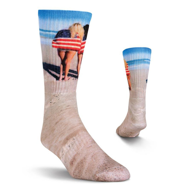 Kurb Mens Americantastic Crew Sock has Sandy Beach Colors and Blue Sky and Waves as background colors to this sock. It features 3 American Women wearing 3 American Flag Towels. This is a great way to show your Patriotic Zeal.
