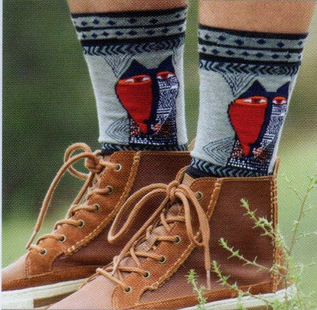 Laurel Burch Mens Native Cat Socks is looking at you like a Native Mask. One Side is all Red with Eyes and some Black. The side of the Cat is White with Black designs and some Red.