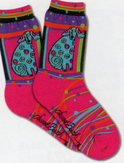 Laurel Burch Matisse Sock is on a field of Bright Magenta. The Dog is Framed and is Teal with Dots all over it. Below the Portrait are lines and Dots of Colors of the rainbow.