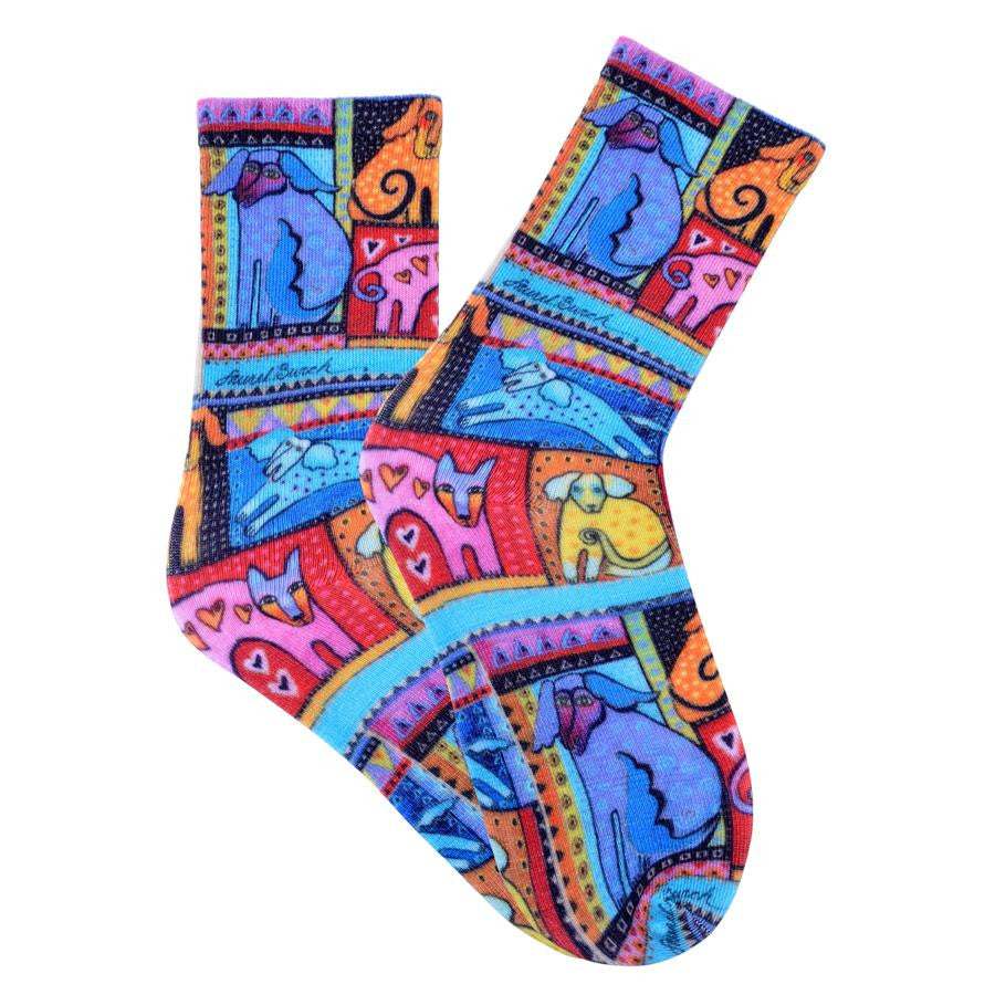Laurel Burch Colorful Dog Socks are on a Red background with Dogs of Different Colors are framed like its own piece of art.