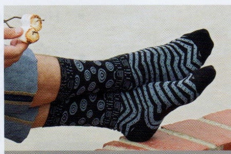 Model wearing Laurel Burch Mens Shapes Socks which are Black background and Shapes of Circles, Lines, Chevrons and Dots.