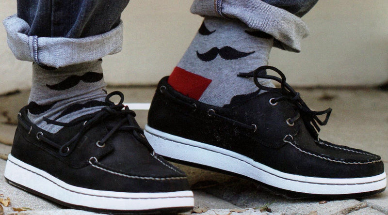 Model wearing Moustache Socks Grey background Black Moustaches Maroon Heels and Toes.