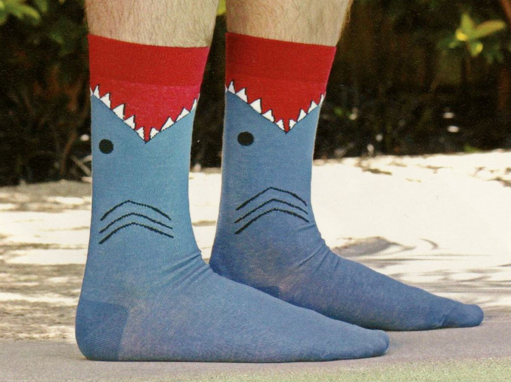 This is a Model wearing K Bell Mens Shark Sock. The Cuff is Maroon met with White and Black for Teeth. Black Eye and Gills then the rest of the Sock is Slate Blue.