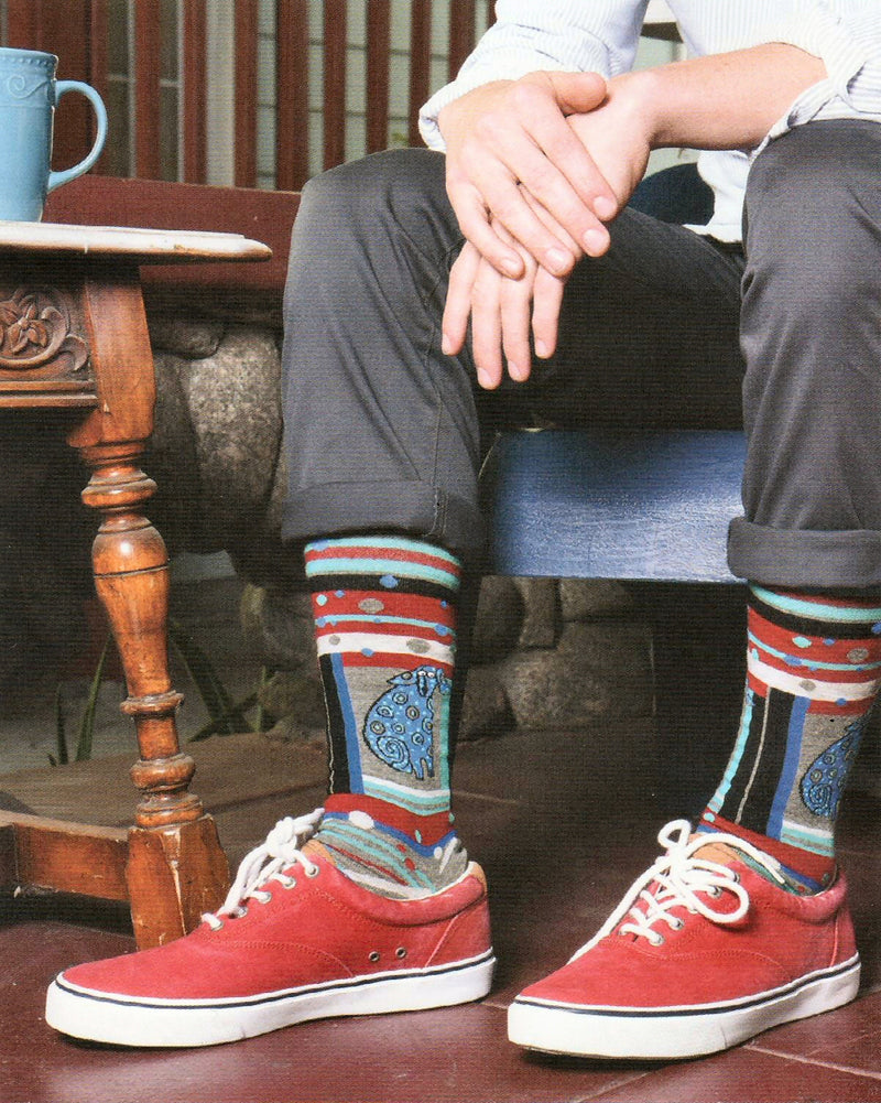 A Model is wearing Mens Laurel Burch Matisse Dog Sock is a Portrait of a Dog in Blues and Greys. In a unique style to favor the Painter Matisse. The socks look great with the Red shoes and Grey pants!