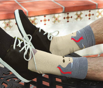This Model is wearing the K Bell Mens Snake Sock with Black Shoes. Showing the Grey top of the Sock and the Sand color of the Snake with white Fangs and Red Tongue.