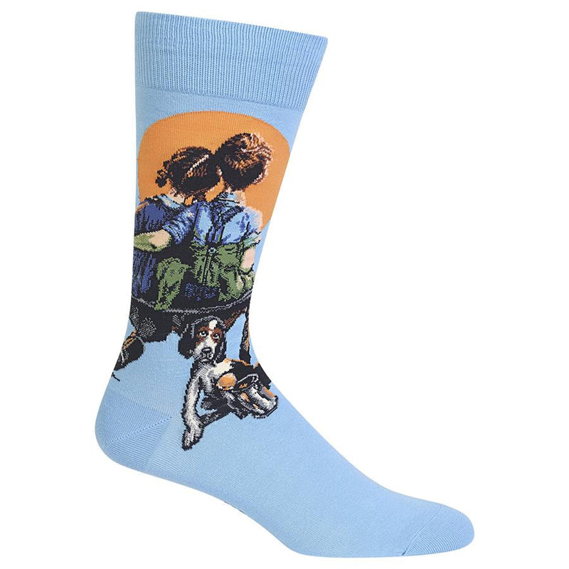 Hot Sox Mens Little Spooners Sock have about a two inch Cuff and then on the Sky Blue background starts the painting. An Orange Sun or Moon depending on which title you like is big in the night sky. The boy and girl are watching it on a makeshift bench. They are spooning together. The dog waits patiently for something to do.