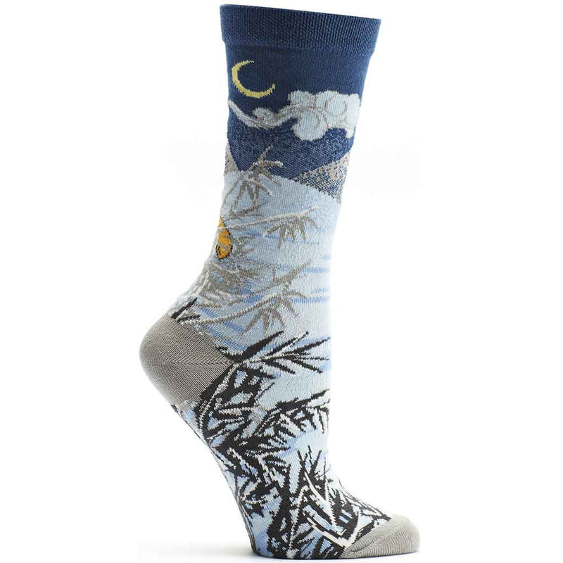 Ozone 4 Seasons Winter Sock starts with a Navy background at the Cuff and below with a Yellow Crescent Moon and Clouds. The Mountain is Snow covered and goes to the bottom where you find a fox hunting for food in snow of white and blues with foliage in Black and Greys.