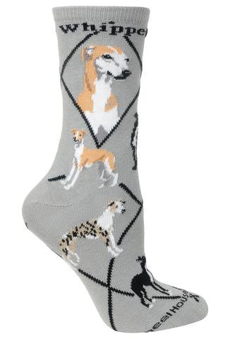 Wheel House Designs Whippet Sock starts on a Grey background and has Black Lines that make Diamonds. On Both side of the Sock reads in bold Black print Whippet. Then there are two Portraits of the Whippet one Frontal and one Profile. All the Poses of the Whippets going down the Sock are Standing but all all different colors That the Whippet can come in there are 18. Some are Black and White, some are mostly Fawn and White.