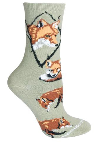 Wheel House Designs Fox on Stone Sock has a Portrait of a Red Fox in a Diamond made of Black Tree Branches. The Colors of Sienna and Rust, White and Light Grey with Black make up the Features of all the Foxes on this Sock. The Poses are of one Laying tightly in a circle and the others Nose to ground on the scent for food.