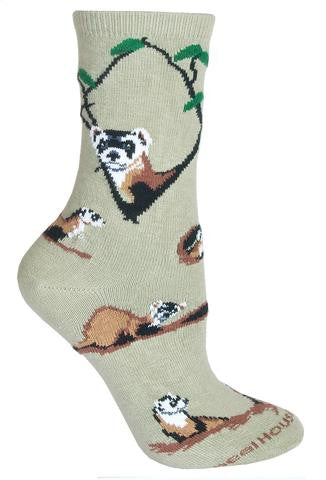 Wheel House Designs Ferret Sock starts on a Stone background with the Ferret Looking out of Tree Branches of Black with Green Leaves. One Portrait is a Profile the other is a Front view. The Ferret is Black and White on its Face and Browns and Black down its thin body to the tail. The poses show the Ferret as a digger and the lover of burrows and holes.