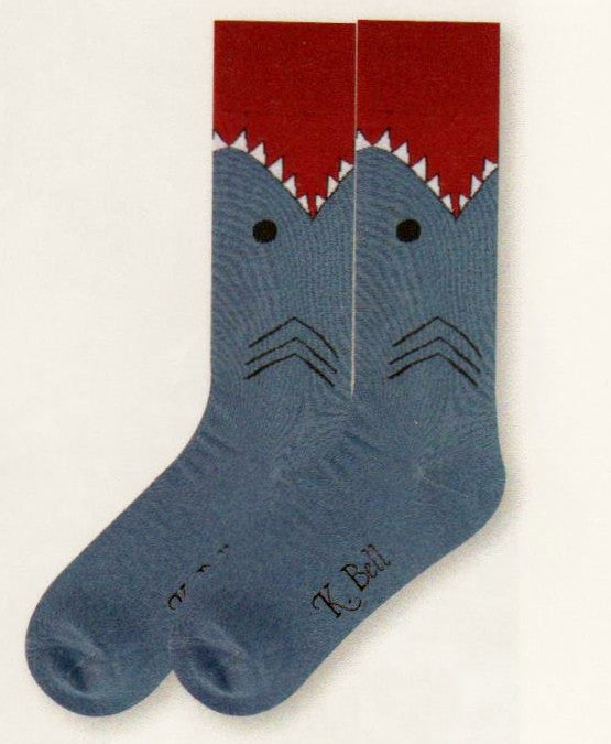 A picture of K Bell Mens Shark Sock starts with a Maroon Mouth, White with Black for Teeth. Black for Eyes and Gills. The rest of the Shark's Body is Slate Blue to the Toes.