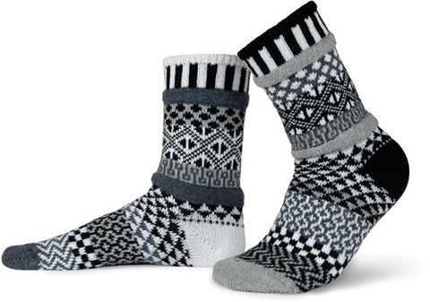 Solmate Socks Stellar Series Midnight Sock is a Mismatched Sock with Black and White, Dark and Light Greys. There are Diamonds and Wavy Lines but also a Pendulum counting down to Midnight.