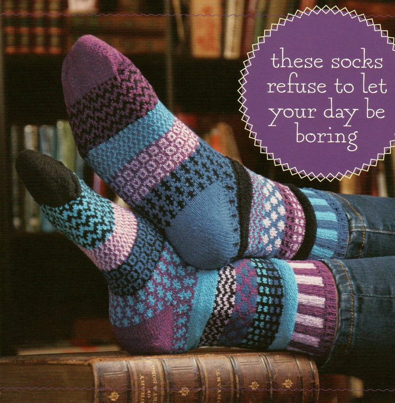 Model from Solmate Socks wearing Vermont Garden Raspberry Sock. The Sign say these socks refuse to let your day be boring.  In purple and blues.