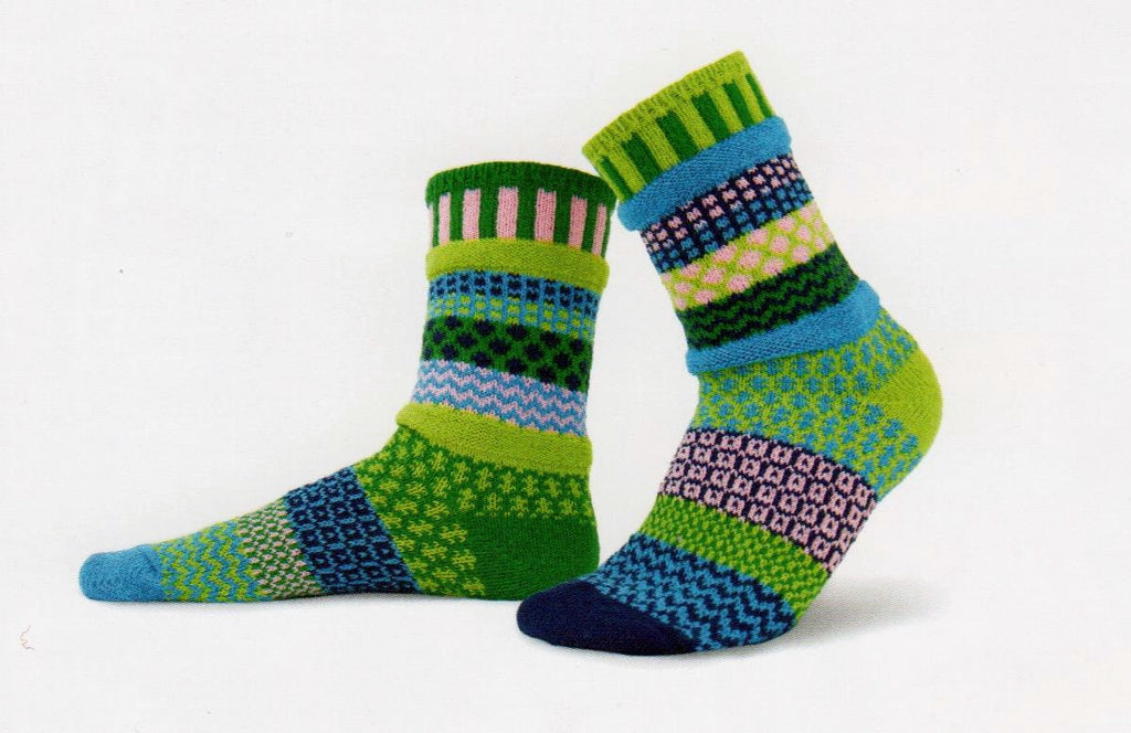 Solmate Socks Vermont Garden Water Lily Sock is Mismatched on Purpose with Brightly Colored Yarns. The colors are Kelly Green, Navy Blue, Pale Pink, Lime Green and Turquoise.