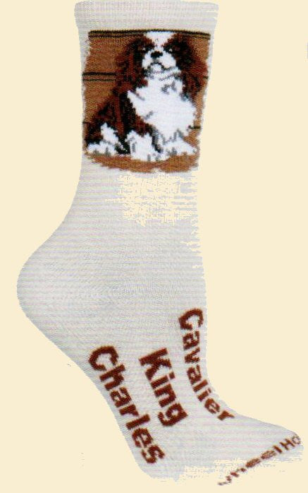 Cavalier King Charles 2014 Sock from Wheel House Designs is on a Natural background on the foot is written Cavalier King Charles and the Welt has the picture of a very cute Cavalier King Charles in Browns and White.