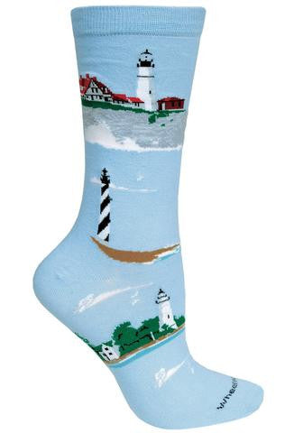 On a Sky Blue background is the Wheel House Designs Lighthouses Sock.  Around the Lighthouses are Clouds and Seagulls in White and Medium Grey. The sock has Four Different Lighthouses. Some were built with living quarters and one shown has none. Colors are Red, Brown Green and Grey with White Waves. Two are White and Black Stripes going around.