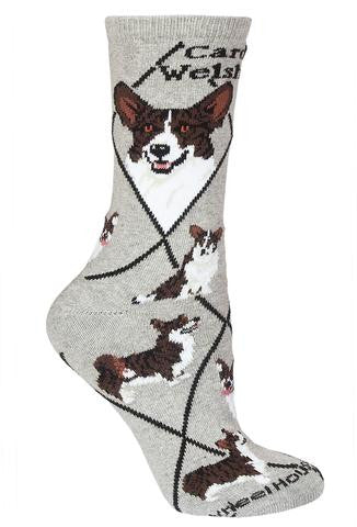 Wheel House Designs Cardigan Welsh Corgi Sock starts on a Grey background with Black Diamonds all over. It has under the Cuff in Bold Black Print Cardigan Welsh Corgi. Then in the First two Diamonds are the Profiles of a Front and Side View. Poses below are of a Show Stance, Running, Sitting, Looking Up for Approval.