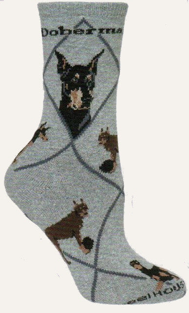 The Doberman Pinscher Dog Socks starts on a Grey background with Dark Grey Lines for Diamonds and for Doberman Pinscher. One profile shows cropped ears the other is natural ears. The poses show one in a stance, one playing with a Black Ball, and one laying down.