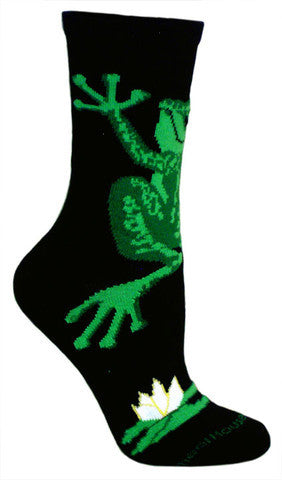 Wheel House Designs Frog Hug Sock starts on a Black Background with a Large Green Frog wrapping itself around your ankle. It is in all different shades of green. Near the Toe is a Lilly Pad with a White Flower on it.