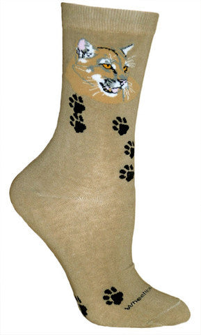 Wheel House Designs Mountain Lion Sock is on a background of Khaki. There are Black Mountain Lion Paw Prints over the sock. The Face of the Mountain Lion is at the top of the Sock in Whites, Black and Sandy Brown with Light Grey. Pink is for mouth and ears.