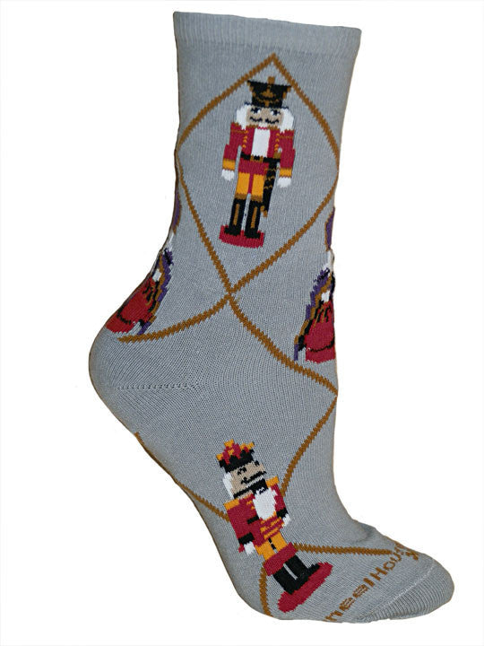Wheel House Designs Nutcracker Sock starts on a Grey background with Mahogany Diamond Lines. The Nutcracker is Black with Red and Orange. White is the Hair, Gloves and Front on the Nutcracker.