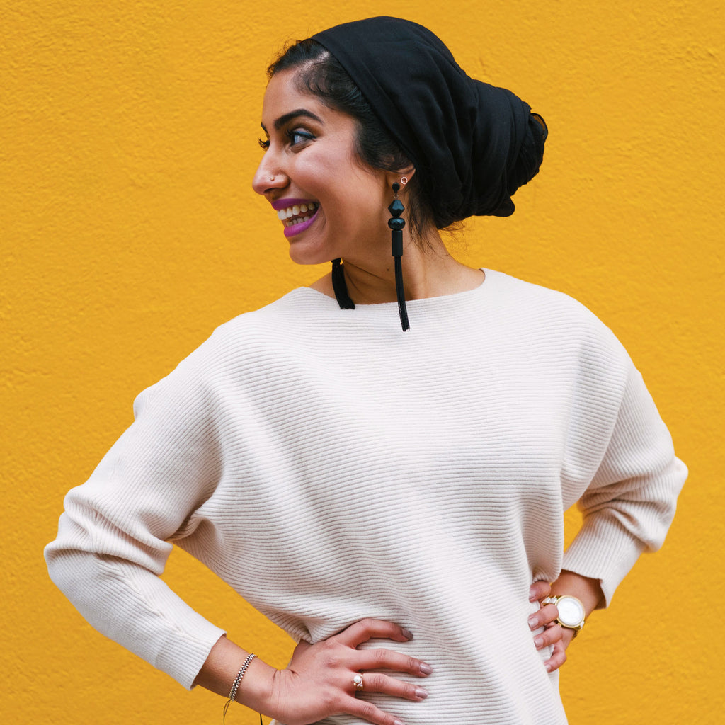 Founder of Sukoon Active, Arshiya Kherani, in a black hijab and cream sweater against a gold background.