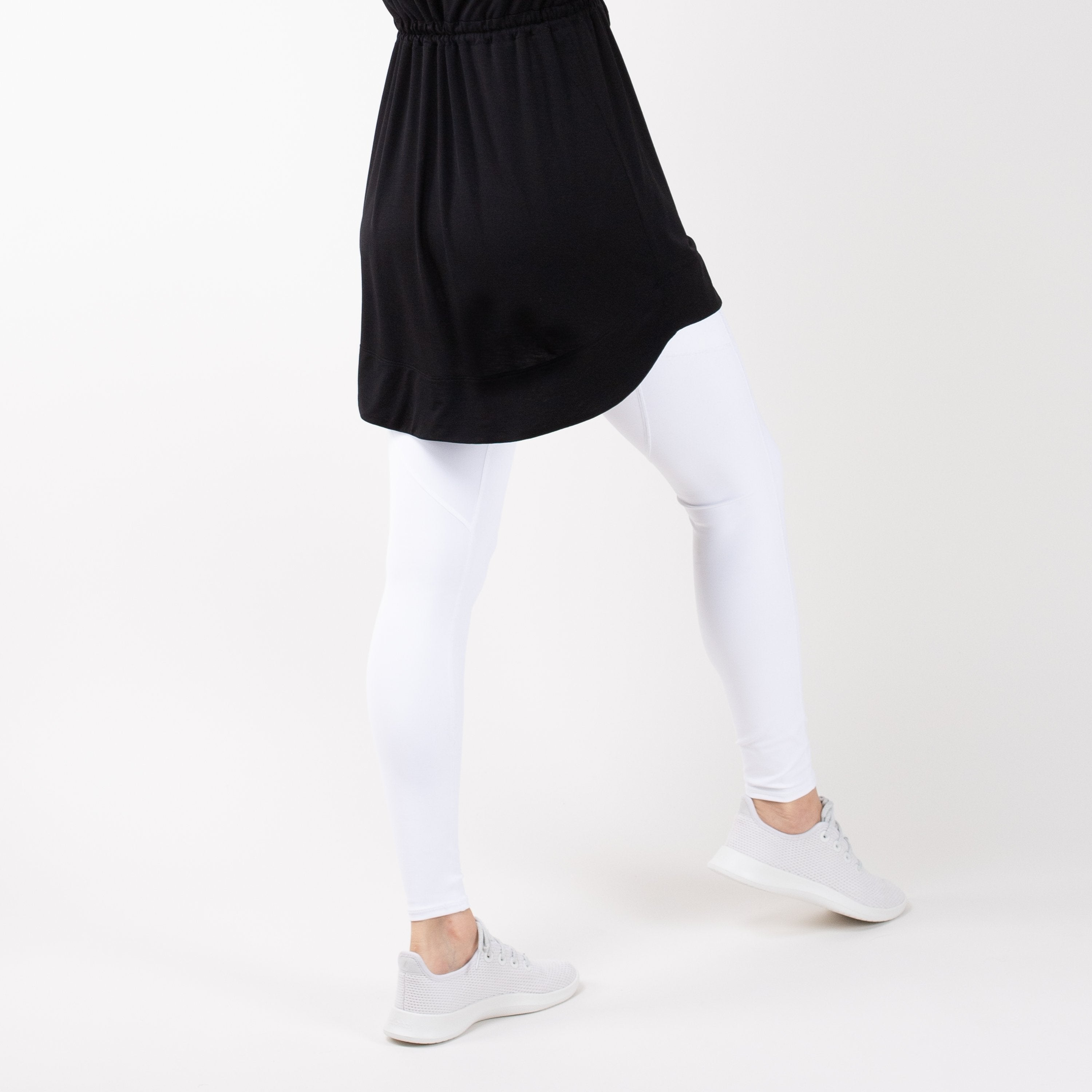 Detail shot of lower-half of a woman in modest, black HAWA drawstring tee shirt and white leggings in front of a white backdrop.