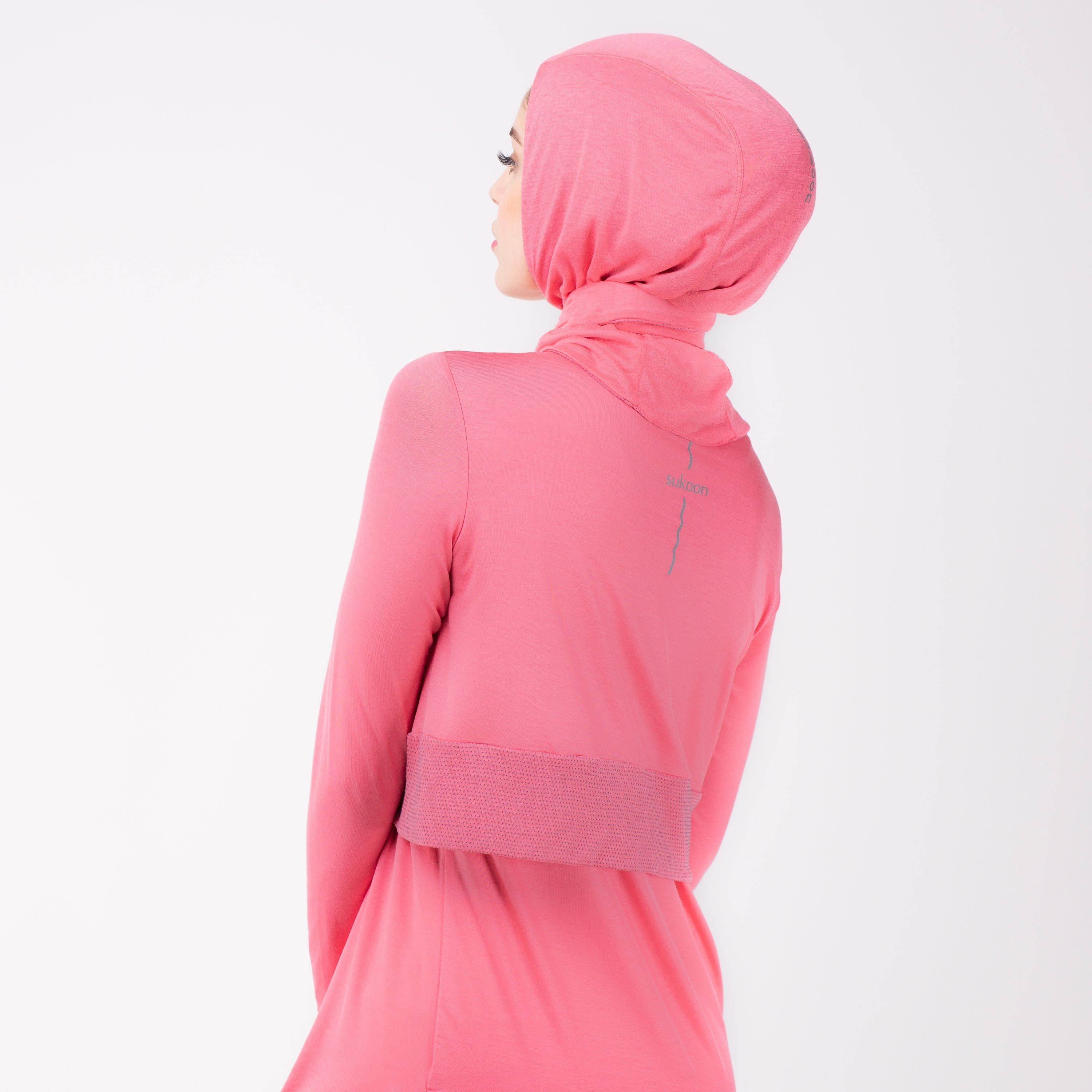 Back detail of a woman in a pink shirt with a matching pink HAWA hijab.
