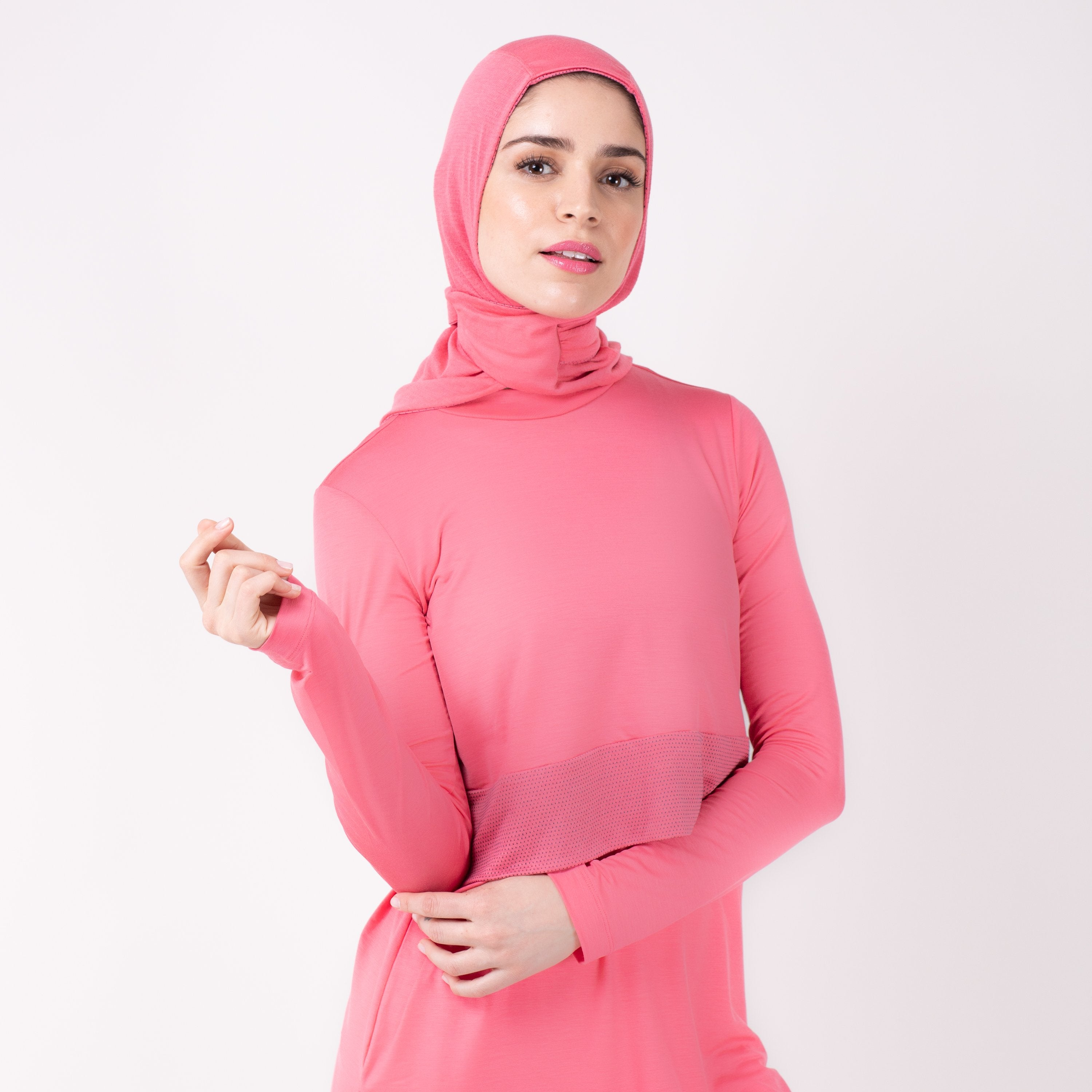 Woman wearing a pink shirt with a matching pink HAWA hijab.