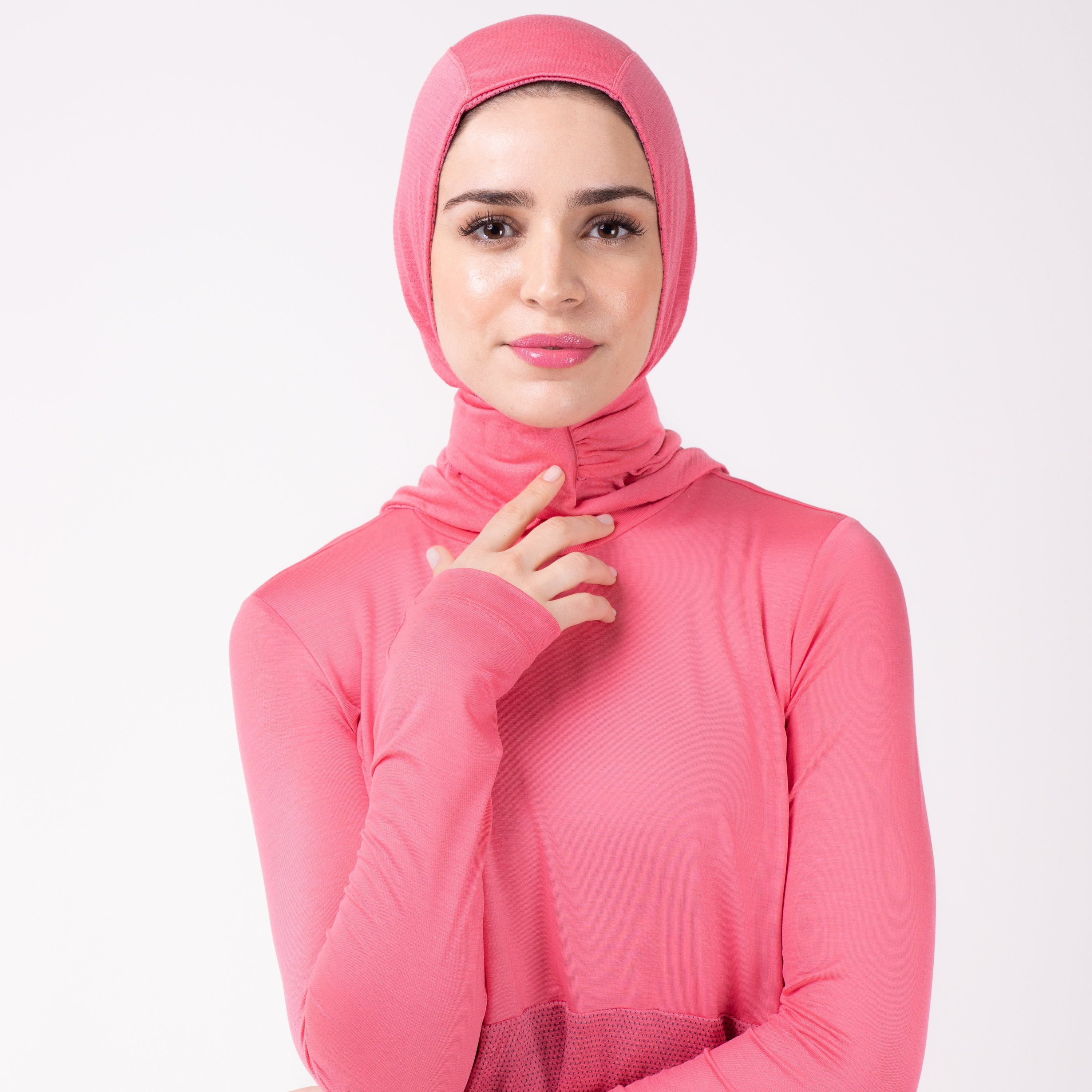 Front detail of a woman in a pink shirt with a matching pink HAWA hijab, touching the closure with her right hand.