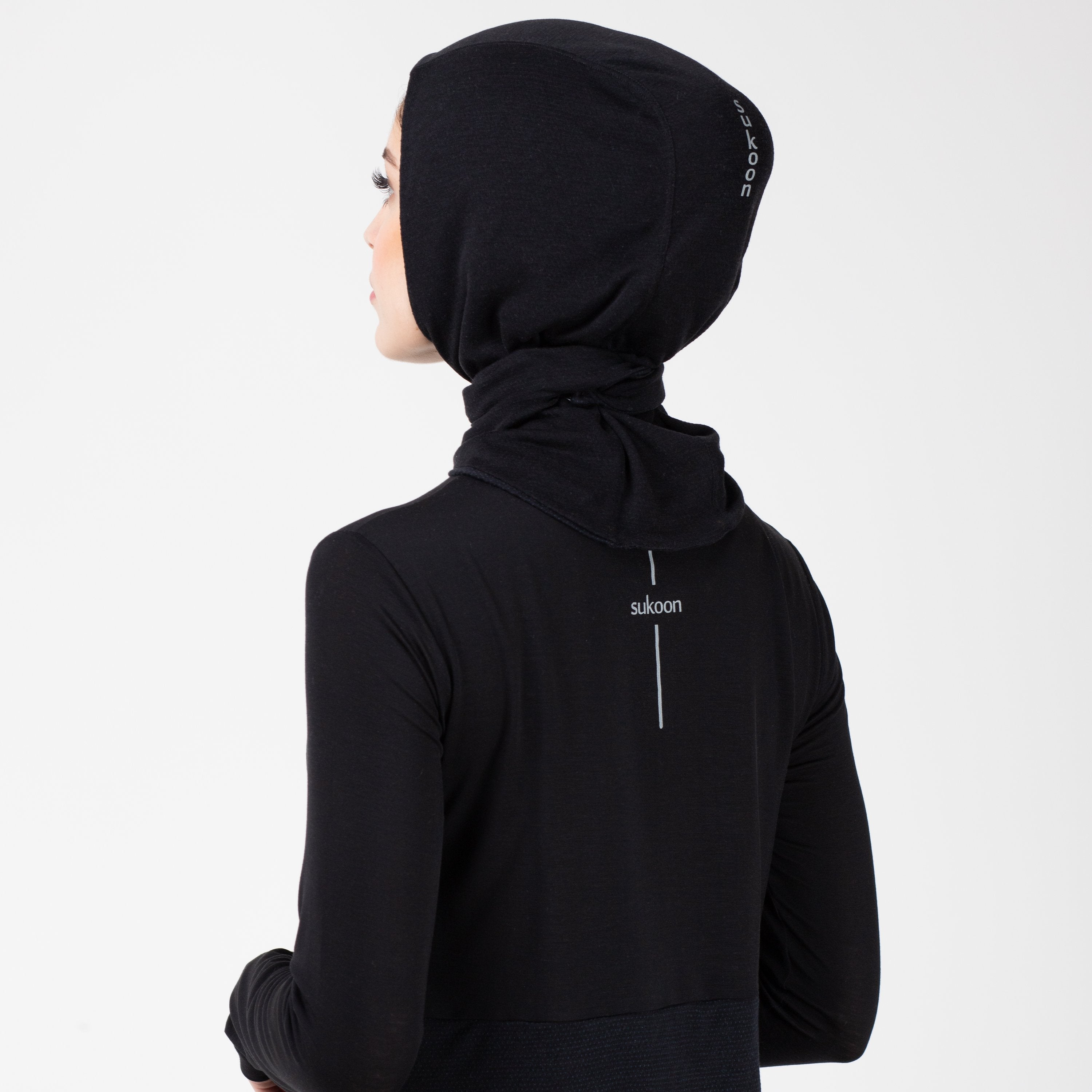 Back detail of a woman in a black shirt with a matching black HAWA hijab.