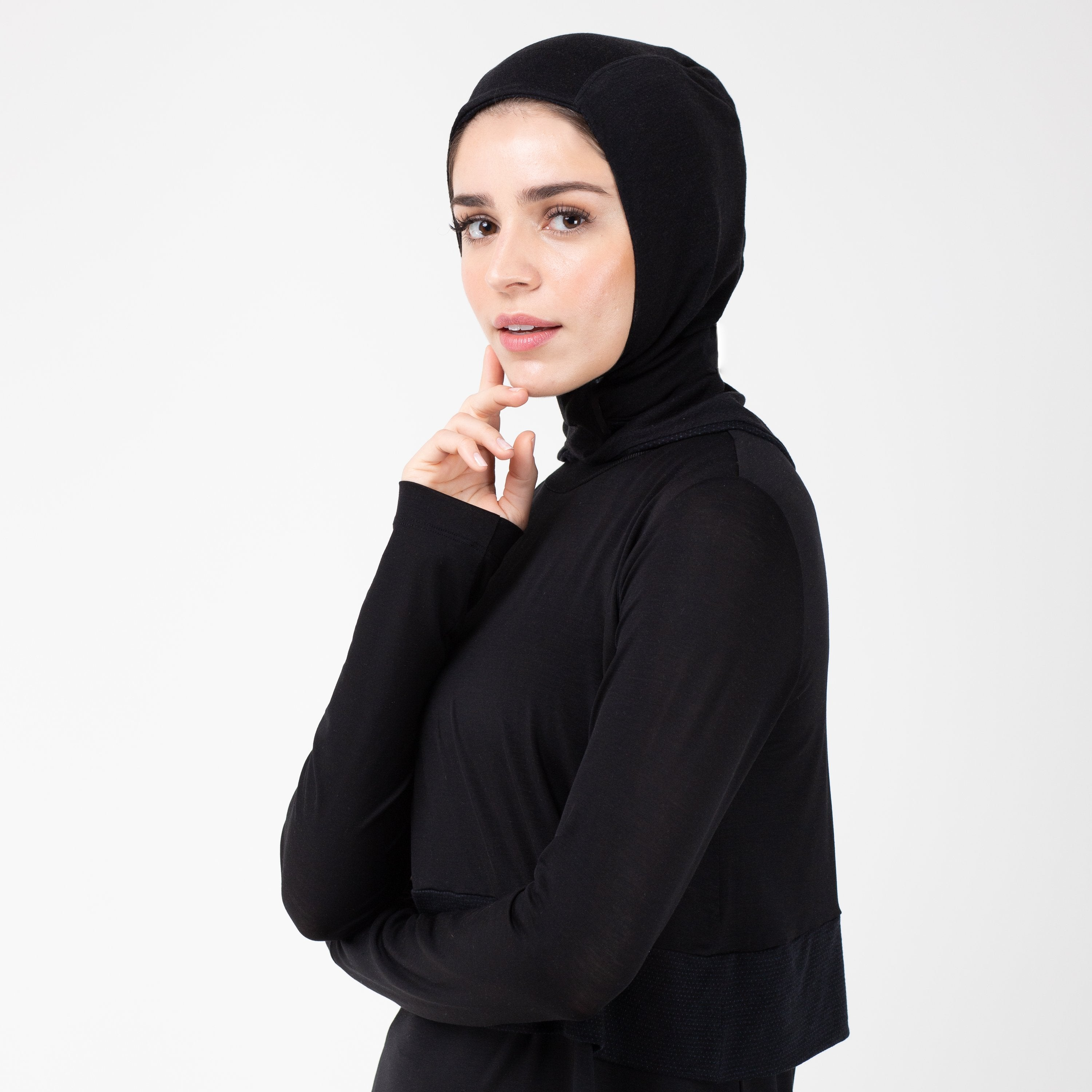 Woman turned to the left wearing a black shirt with a matching black HAWA hijab touching her face with her right hand.