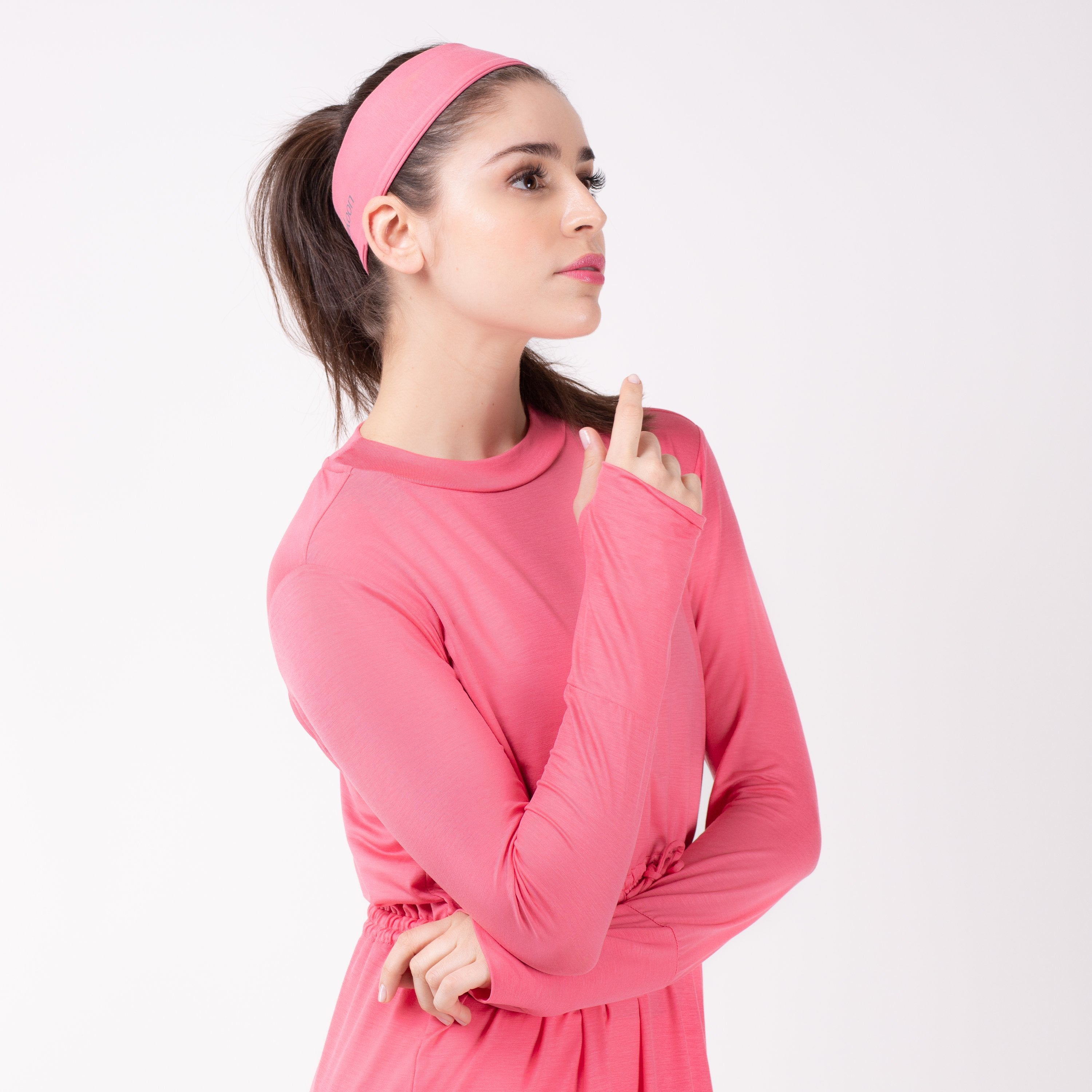 Woman looking right in pink shirt with matching pink HAWA headband.