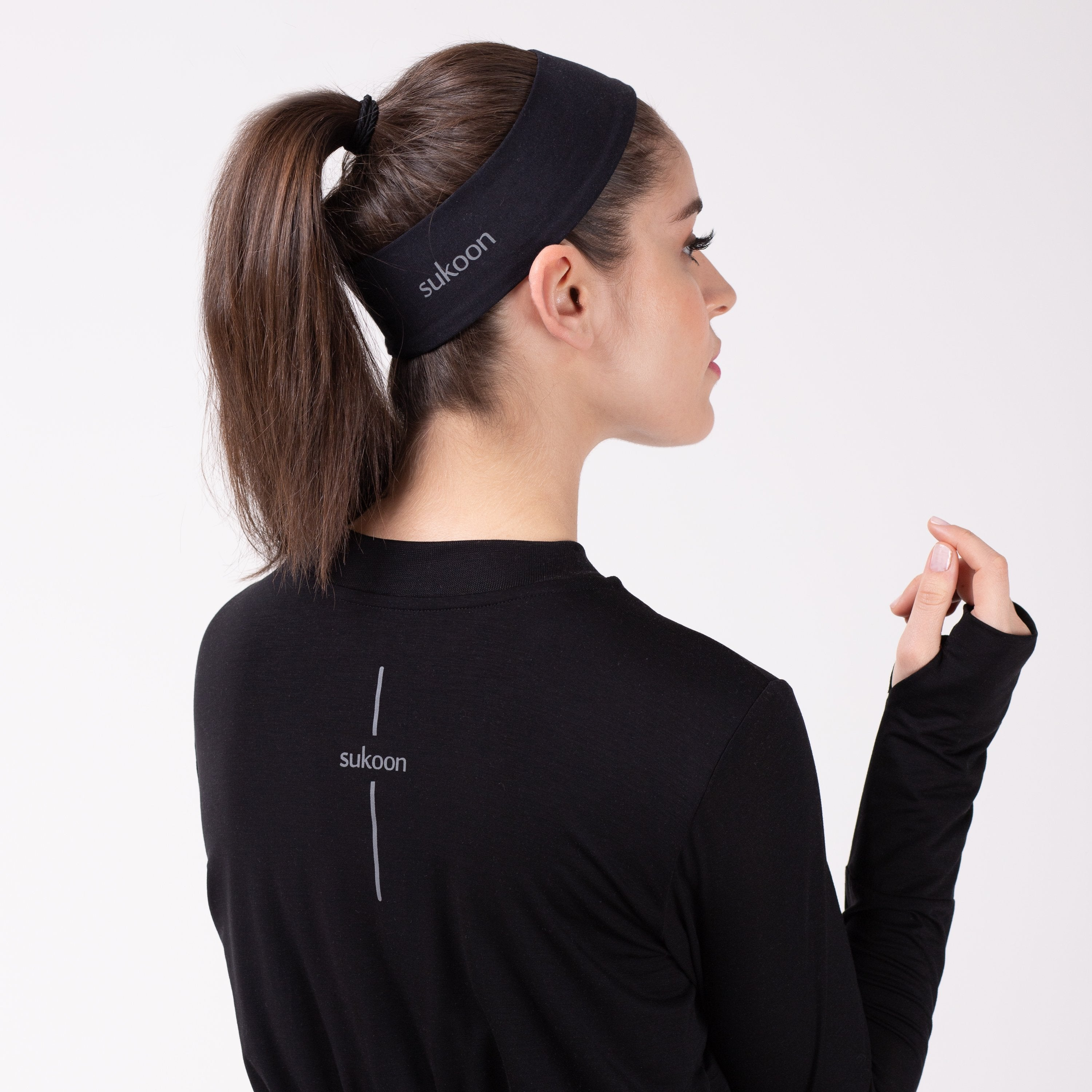 Back detail of woman in black shirt with matching HAWA headband.