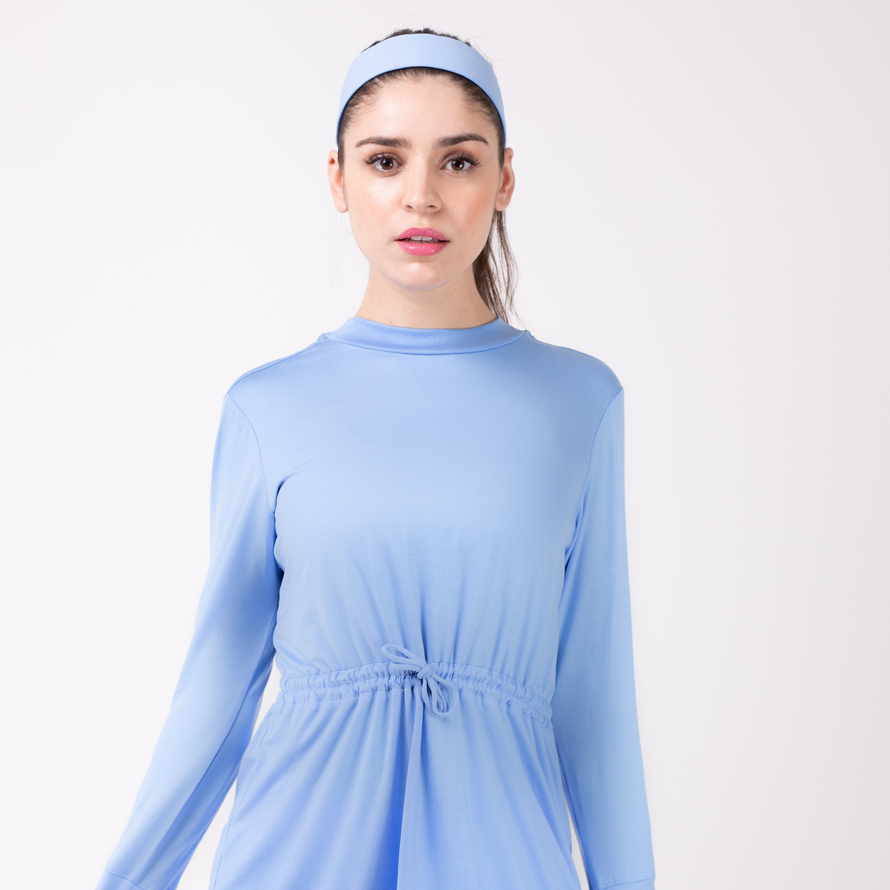Woman in light blue shirt with matching sky blue HAWA headband.