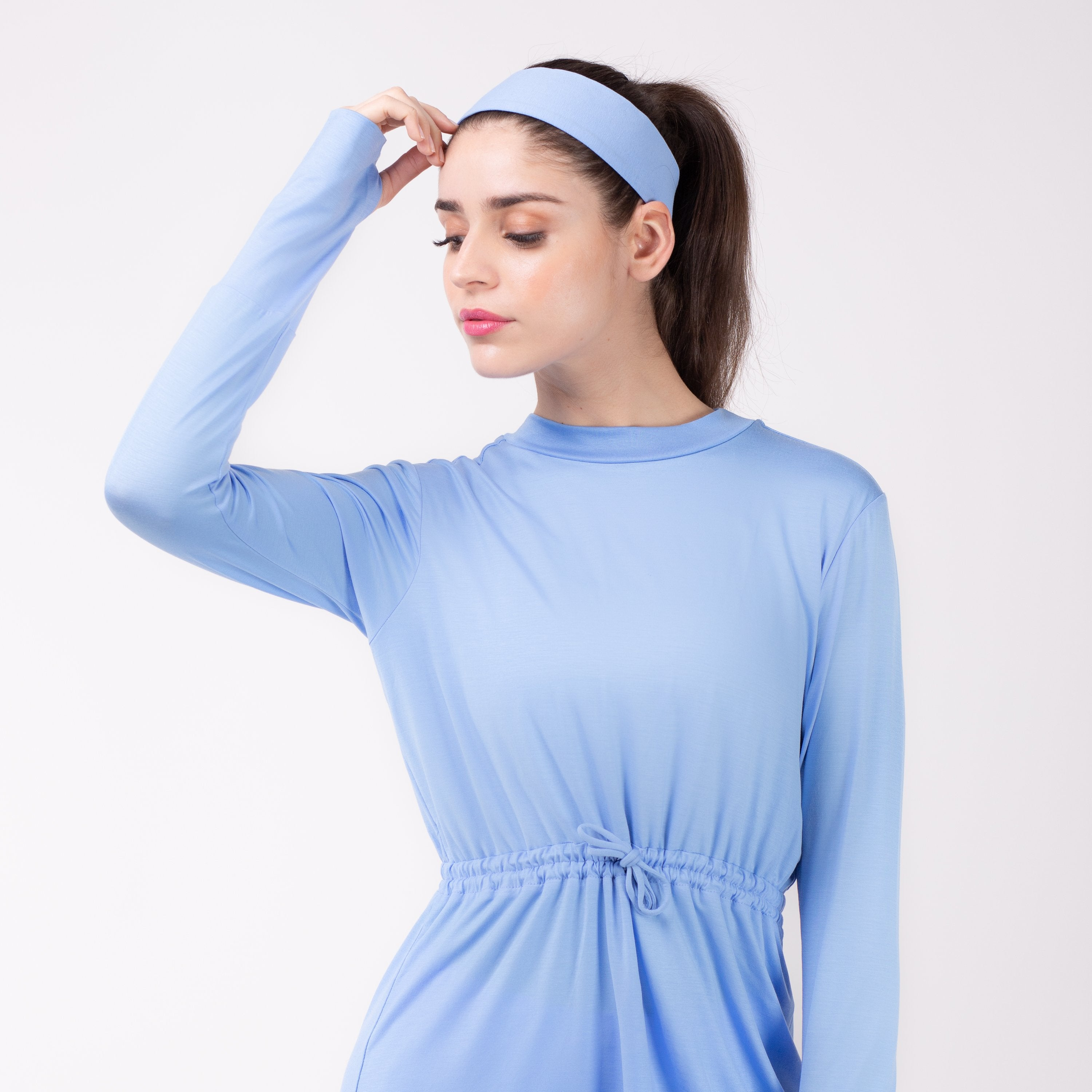 Woman looking left in sky blue shirt with matching sky blue HAWA headband.
