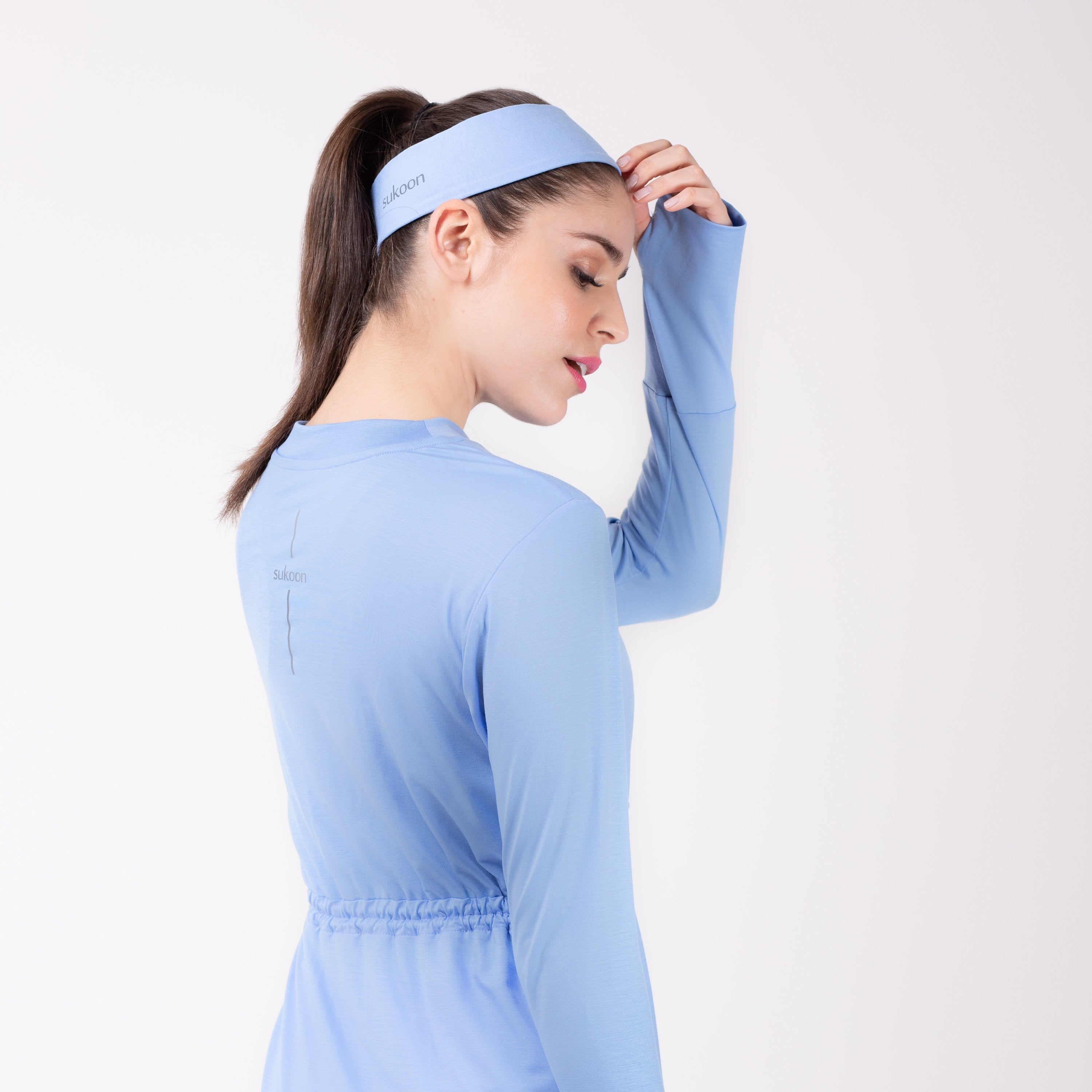 Back detail of woman in sky blue shirt with matching sky blue HAWA headband.